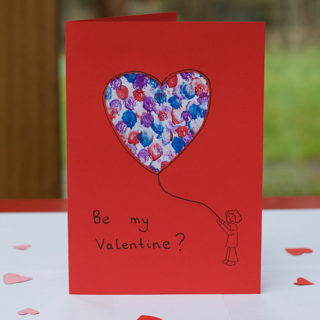Red card, with a person holding a heart shaped balloon decorated with coloured finger paints.